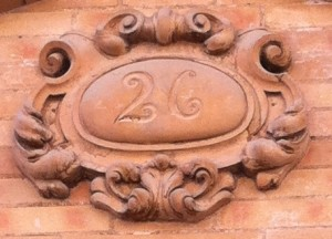 A baroque 26, shaped in terracotta on the brickwork, on an old house in the historic centre of Seville by Jane Chittenden